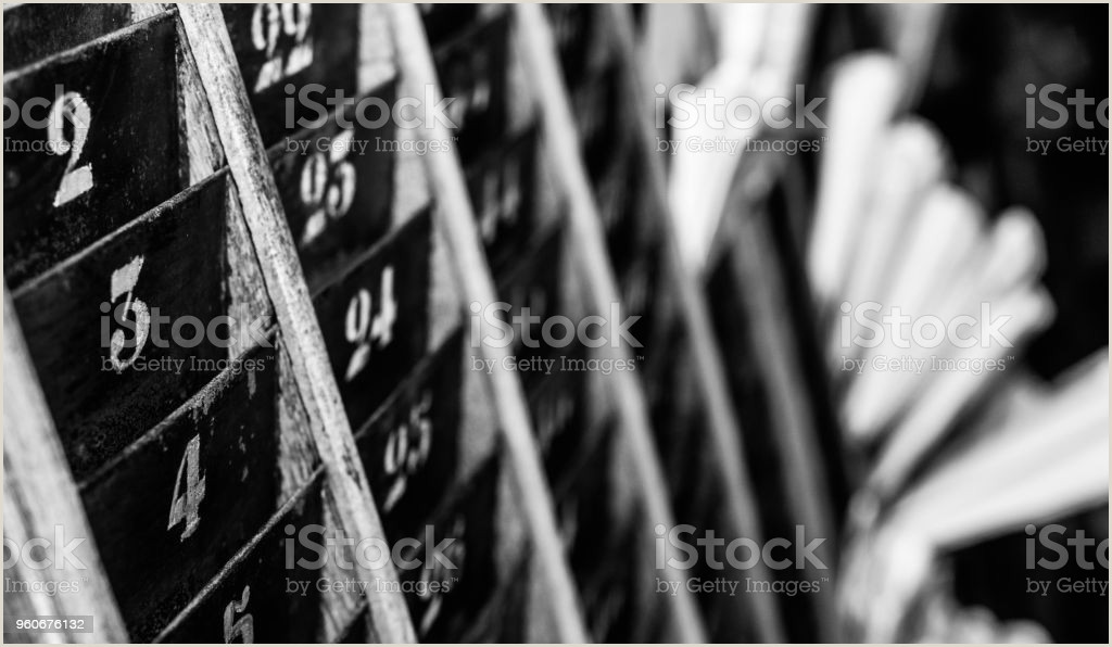 Buisness Caeds Numbered Old And Faded Time Clock Punch Card Wall Rack With Papers In The Distance Stock Download Image Now